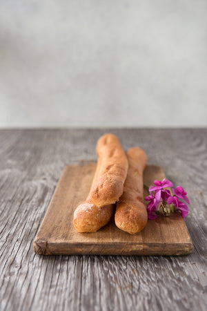 Load image into Gallery viewer, 3 whole gluten free baguettes stack on cutting board with flowers