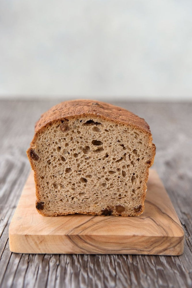 cut face loaf gluten free cinnamon raisin bread on wood cutting board