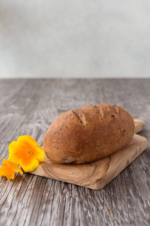 Load image into Gallery viewer, whole loaf gluten free Multigrain Sourdough on wood board with flower