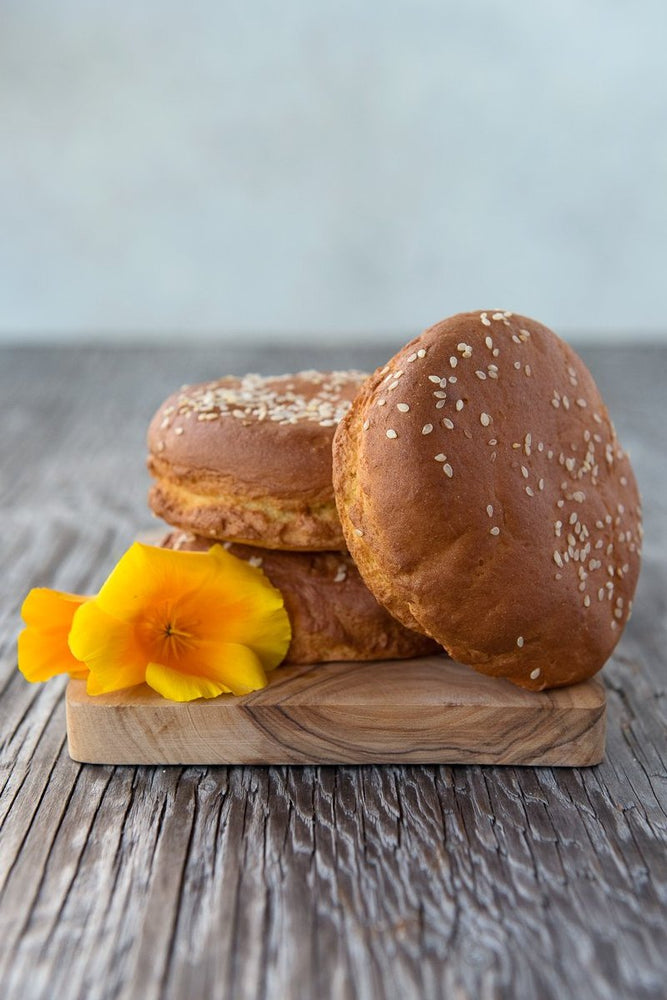 Load image into Gallery viewer, pile gluten free hamburger buns with sesame seeds on wood board with flowers