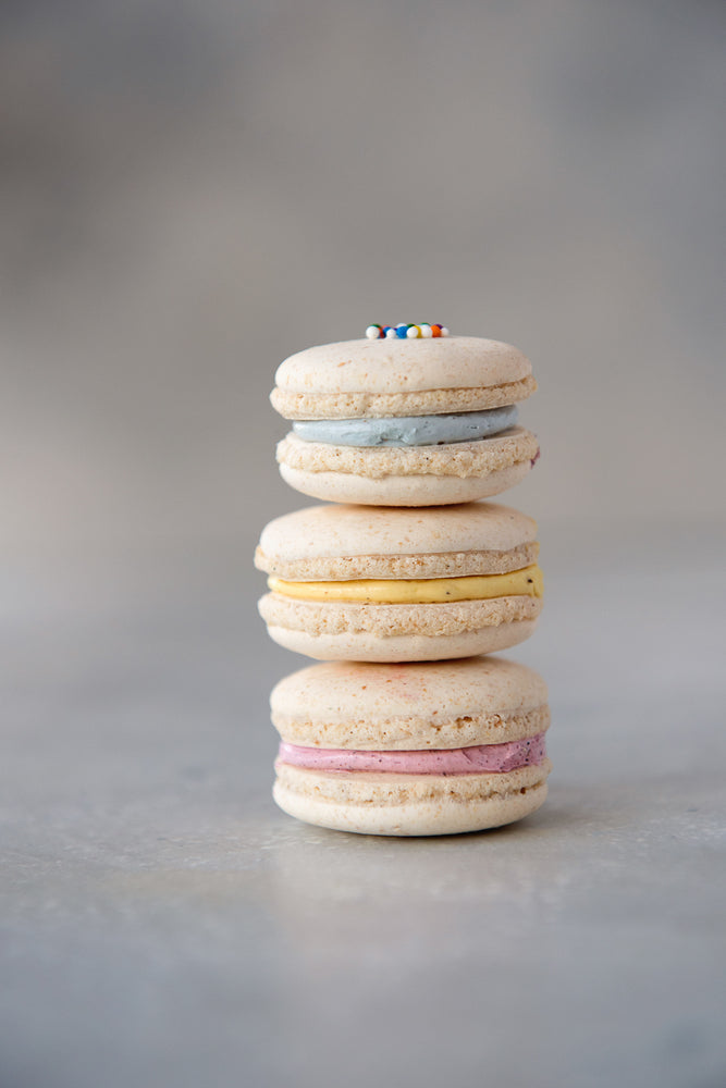 stack of 3 gluten free macarons, buttercream filling, blue, yellow, pink