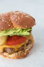 close view gluten free hamburger with lettuce tomato cheddar and dijon mayo