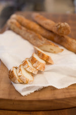 gluten free baguette slices on white cloth on wood cutting board