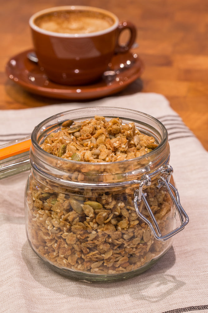 Load image into Gallery viewer, gluten free vegan granola in glass jar displayed with latte