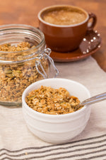 gluten free butter granola in white bowl with spoon, displayed with latte and jar granola