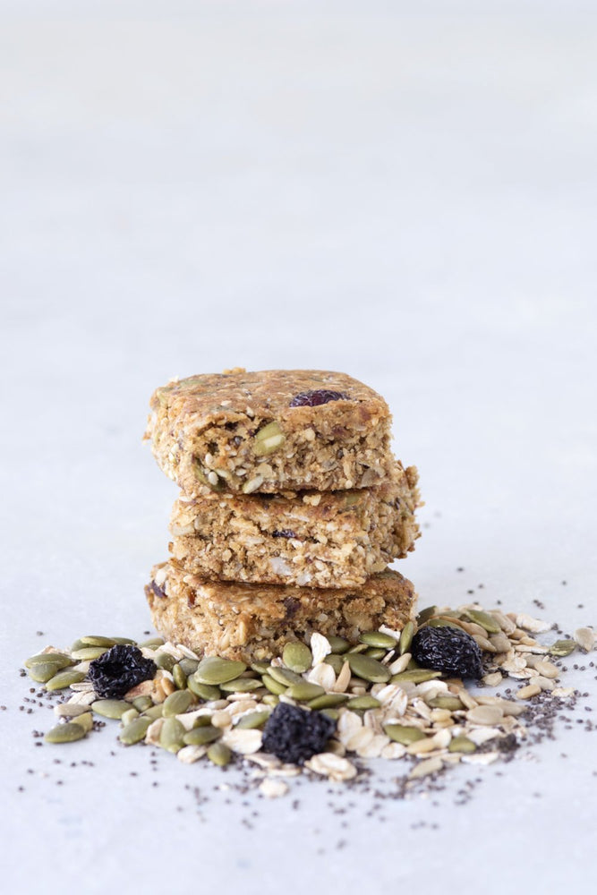 stack 3 gluten free granola bar squares displayed with raisins sunflower seeds oats and poppy seeds