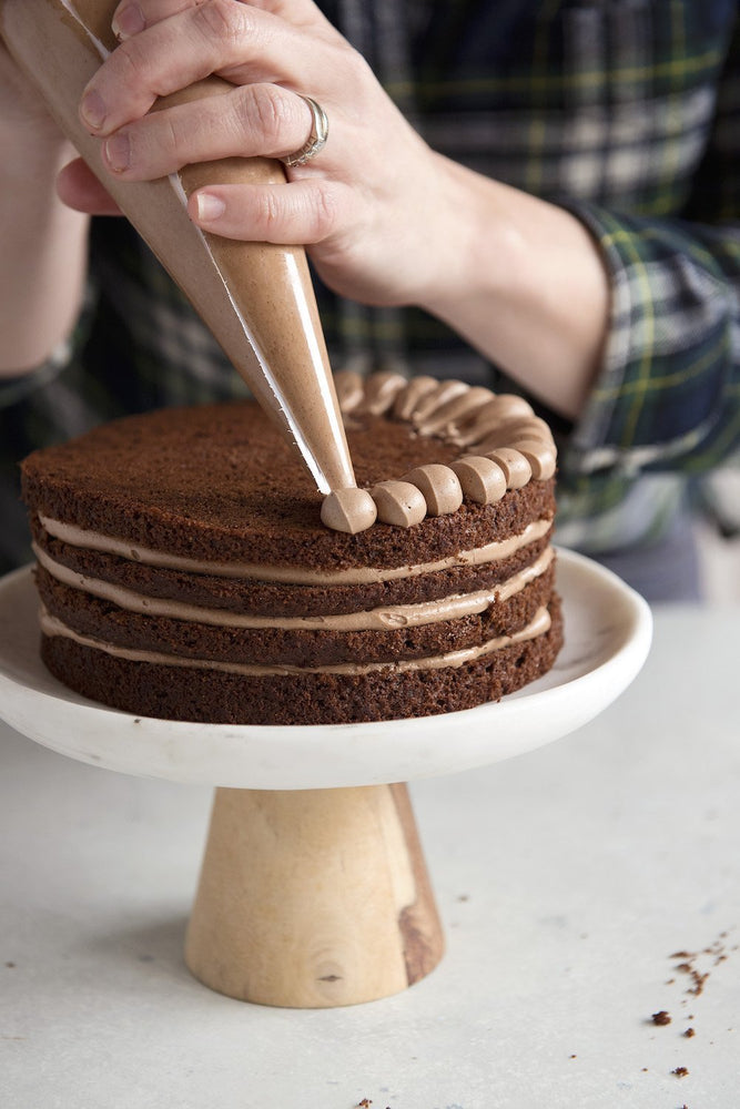 Load image into Gallery viewer, piping frosting on a gluten free cake