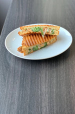 gluten free grilled panini cut in half on plate, roasted garlic lemon chicken, pesto, arugula, provolone