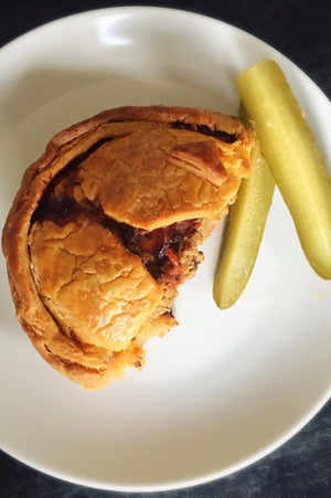 Load image into Gallery viewer, top view half gluten free cheeseburger pie shown with pickles on a plate
