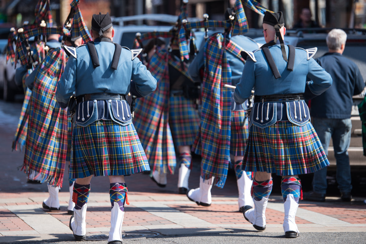 Bagpipers wearing blue and red kilts