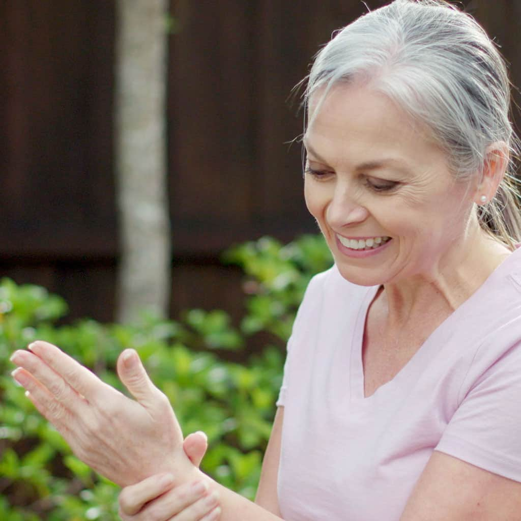An older woman in a pink shirt smiling and holding her wrist