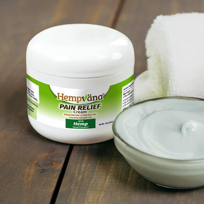 A jar of Hempvana Pain Relief Cream next to a towel and a small bowl of product