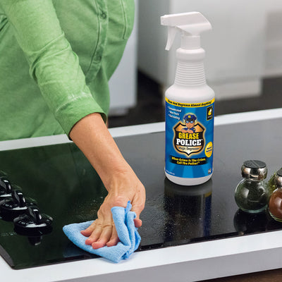 A woman's arm wiping a countertop with a cloth next to a bottle of Grease Police