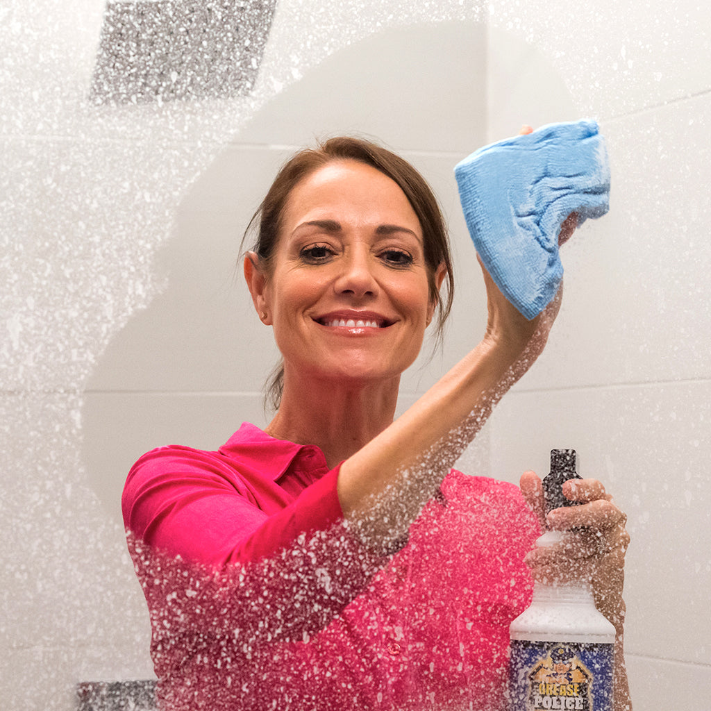 A woman wiping a shower door with a cloth while holding a bottle of Grease Police