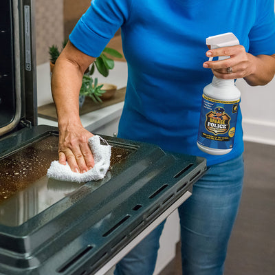 A woman wiping the inside of an oven door with a cloth while holding a bottle of Grease Police