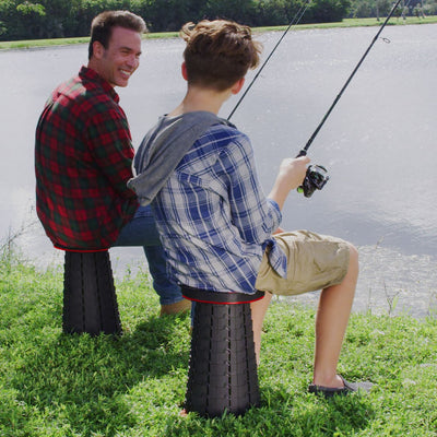 Man and boy sitting on Pop-Up Stool fishing at a lake