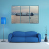 A ship with striped dolphin jumping outside the sea at sunset multi panel canvas wall art