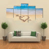Heart with arrow, as love sign, drawn on the beach shore multi panel canvas wall art