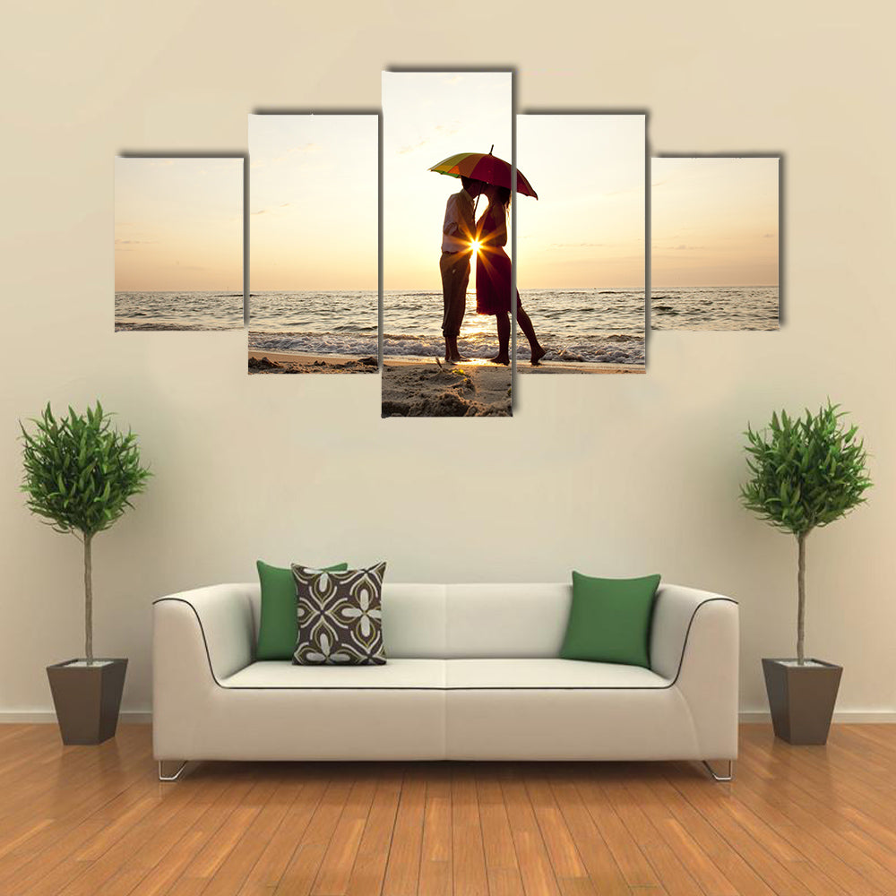 Couple kissing under umbrella at the beach in sunset multi panel canvas wall art