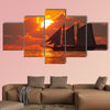 A boat sailing in front of a beautiful sunset in Key West, Florida multi panel canvas wall art