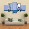 Back view of two windsurfers in action moving parallel to eath other Multi panel canvas wall art