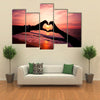 Silhouette hand in heart shape with sunrise in the middle and beach background multi panel canvas wall art
