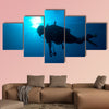 Silhouette of diver with sun disk behind Multi panel canvas wall art