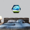 Earth rising in space over a green grassy field hexagonal canvas wall art