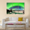 Spectacular display of intense Northern Lights or Aurora borealis or polar lights forming green arc over snowy winter landscape Multi panel canvas wall art