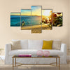 Young happy couple enjoying a beautiful sunset multi panel canvas wall art