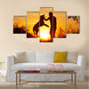 Young man with his yellow labrador retriever in nature - back lit  Multi panel canvas wall art