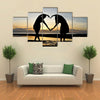 Two girls make heart with sea and sun down background multi panel canvas wall art