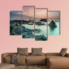 Coloring sky during sunrise with rocks on the beach wall art