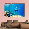 Female scuba diver swimming under water Multi panel canvas wall art