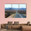 A paved road over rolling hills in a desert landscape in canvas wall art