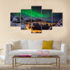 A man looking at the Northern lights over Reine, Lofoten islands, Norway Multi panel canvas wall art