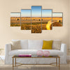 Freshly cropped, farm land hay bales on a sunset Multi panel canvas wall art