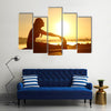Silhouette of a fitness woman stretching at sunset with the sun in the background, Multi panel canvas wall art