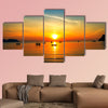 Silhouette of fisher man's boats on the tropical sea with colorful sunrise wall art
