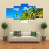 Amazing tropical beach with palm tree entering the ocean against Azur Ocean, gold sand and blue sky Multi panel canvas wall art
