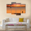 Beach sunset scene in Mozambique with fisherman and small sailboat Multi panel canvas wall art