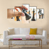 Closeup photo of male hand holding black horse chess piece multi panel canvas wall art