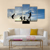 Silhouette boys playing football at sunset Multi panel canvas wall art