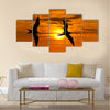 Two birds flying silhouette with a clowing beautiful orange and yellow sunset beaming in the background Multi panel canvas wall art