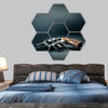 Gun sitting on a table with bullet shells hexagonal canvas wall art