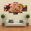 Italian pizza with pepperoni tomatoes olives basil and red wine on wooden table Top view Multi panel canvas wall art