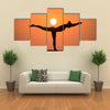 Warrior pose from yoga by woman silhouette on sunset Multi panel canvas wall art