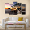 Rear-side view of a luxury car on sunset Multi panel canvas wall art