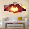 Heart shape making of hands against bright sea sunset multi panel canvas wall art