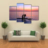 Silhouette of a yoga trainer balancing on the water on the paddle board over beautiful purple sunset Multi panel canvas wall art